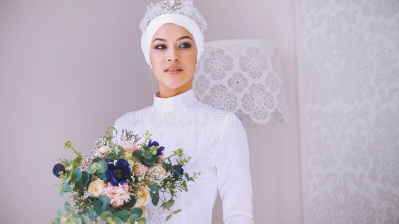 Красивая модель в белом мусульманском платье свадьбы и bridal головной убор с цветками стоковые фотографии rf