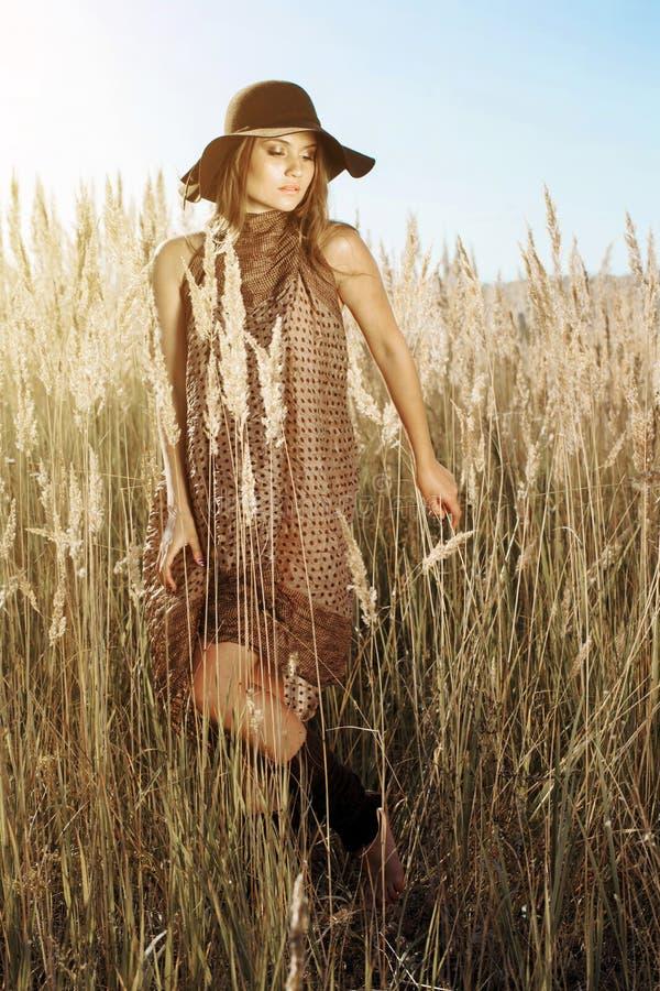 Красивая модель в шляпе идя через tallgrass на золотом часе стоковое фото rf