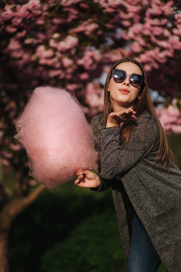 Красивая модель каштановых волос держит конфету хлопка в руках и дает поцелуй Молодая женщина с розовой конфетой хлопка стоковое фото
