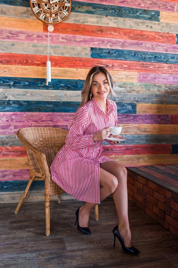 Красивая модная белокурая женщина в розовом striped платье и наслаждается вашим кофе утра Счастье, положительные эмоции, образ жи стоковая фотография
