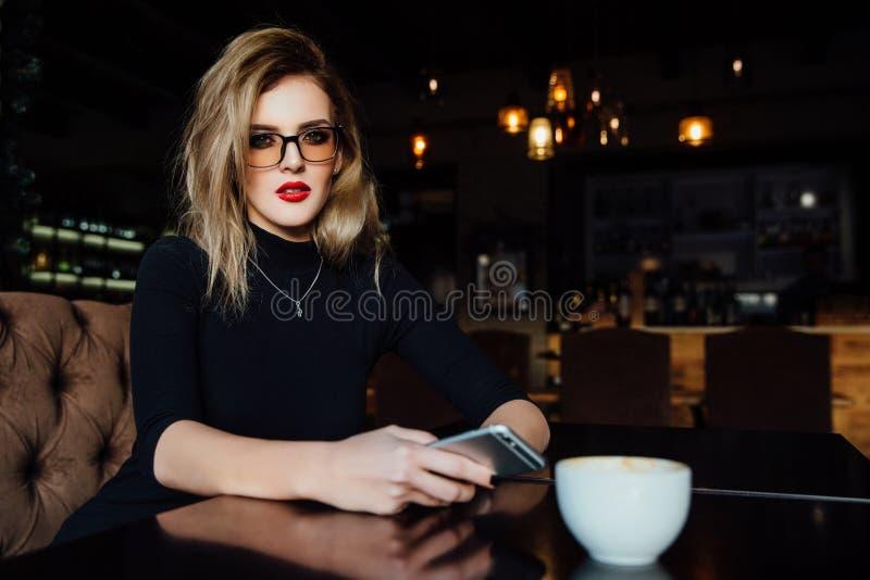 Красивая модная стильная девушка сидит в кафе с чашкой кофе стоковое фото rf