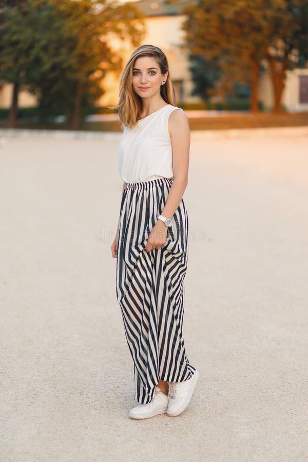 Красивая, модная усмехаясь девушка представляя в стильной, женственной юбке стоковые изображения