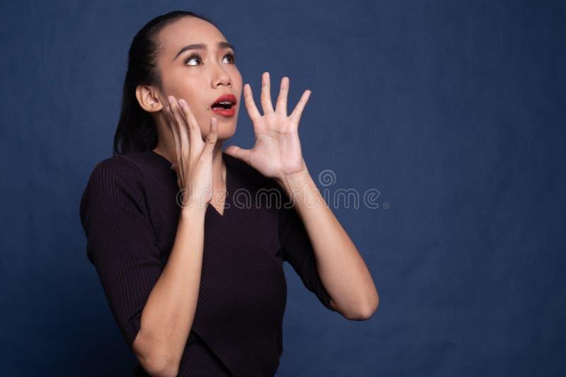 Красивая молодая азиатка шокирована и смотрит вверх стоковое фото