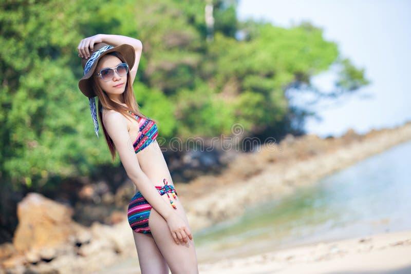 Красивая молодая азиатская женщина в бикини ослабляя на пляже, концепции летних каникулов перемещения стоковые изображения rf