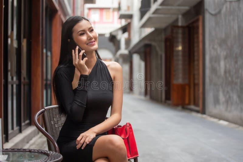 Красивая молодая азиатская женщина в черном платье сидя в кафе кофе вызывая со смартфоном счастливая элегантная дама сидя дальше стоковое фото