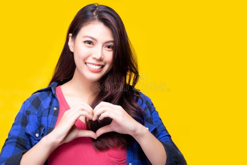Красивая молодая азиатская женщина давая любовь или сердце клиенту или людям путем использование рук для делать сердце сформирова стоковое изображение