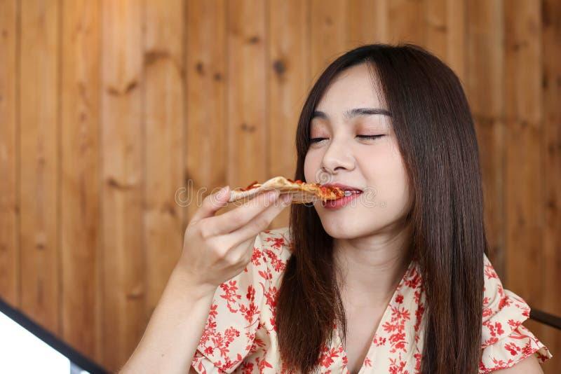 Красивая молодая азиатская женщина есть очень вкусную или yummy пиццу стоковые фото