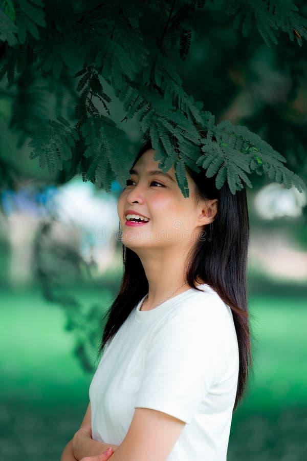 Красивая молодая азиатская женщина китайская насладиться ослабить в зеленой вертикали портрета предпосылки природы стоковая фотография