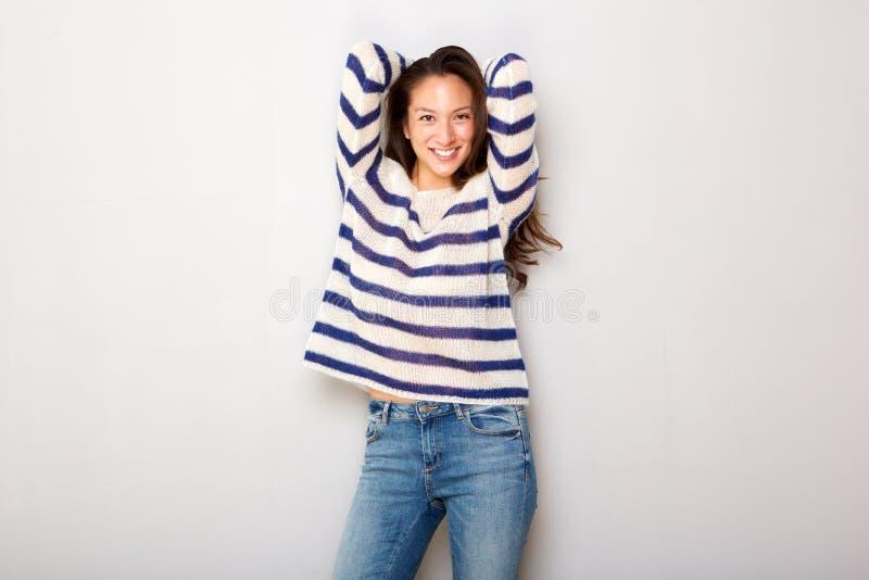 Красивая молодая азиатская женщина смеясь с руками за головой серой стеной стоковое изображение