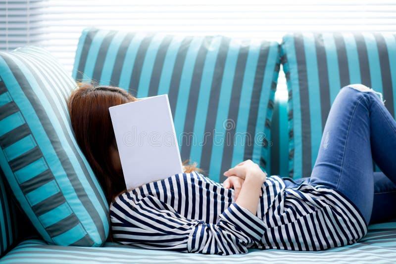 Красивая молодая азиатская женщина спать на софе при книга покрывая ее сторону потому что книга чтения с подготавливать экзамен к стоковое фото rf