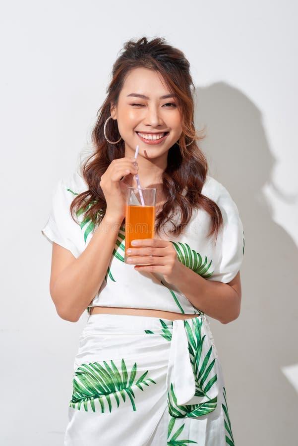 Красивая молодая азиатская женщина с апельсиновым соком в тропической рубашке на белой предпосылке стоковые фото
