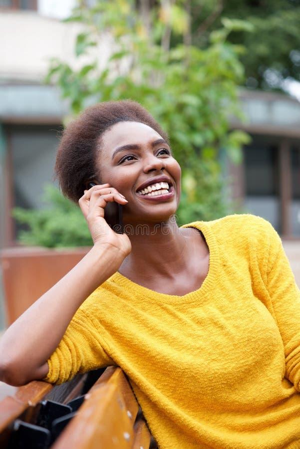 Красивая молодая Афро-американская женщина говоря на мобильном телефоне outdoors стоковое изображение rf