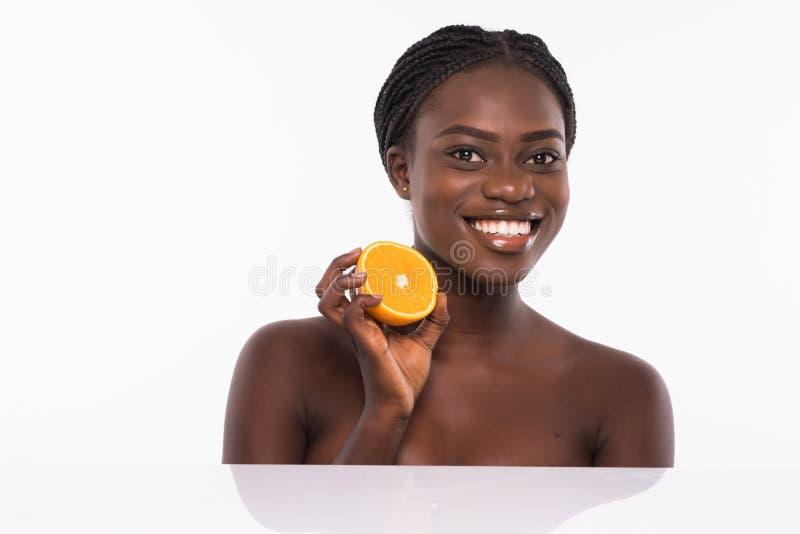 Красивая молодая Афро-американская женщина изолированная на белой предпосылке Девушка Афро и концепция диеты с оранжевым плодом r стоковая фотография