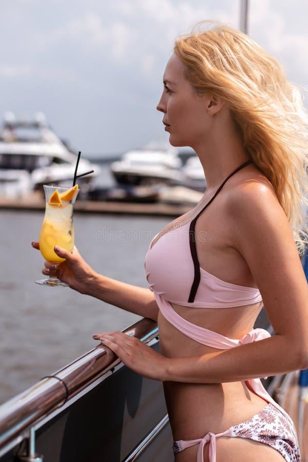 Красивая молодая белокурая девушка в розовом коктейле напитков бикини с соком на курорте стоковые изображения rf