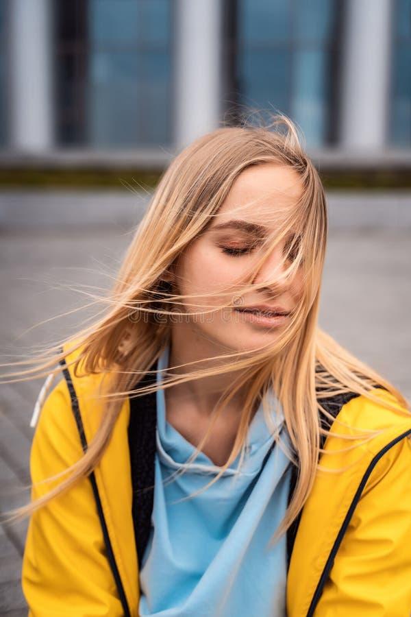 Красивая молодая белокурая женщина на улице, представляя с ветром в ее волосах стоковое фото