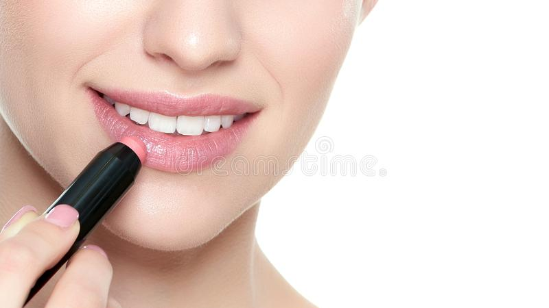 Красивая молодая белокурая женщина при сексуальные полные губы прикладывая коралл красит губную помаду Портрет красоты изолирован стоковые фотографии rf