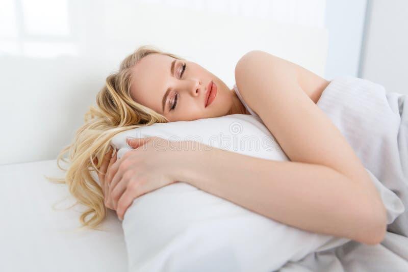 красивая молодая белокурая женщина спать на белой подушке стоковая фотография
