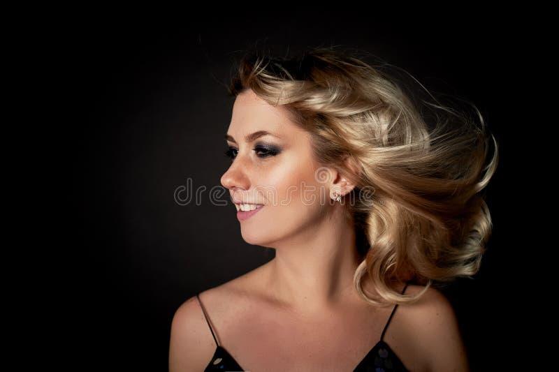 Красивая молодая белокурая женщина с профессиональным составом Smokey наблюдает Волосы порхая в танце стоковое фото