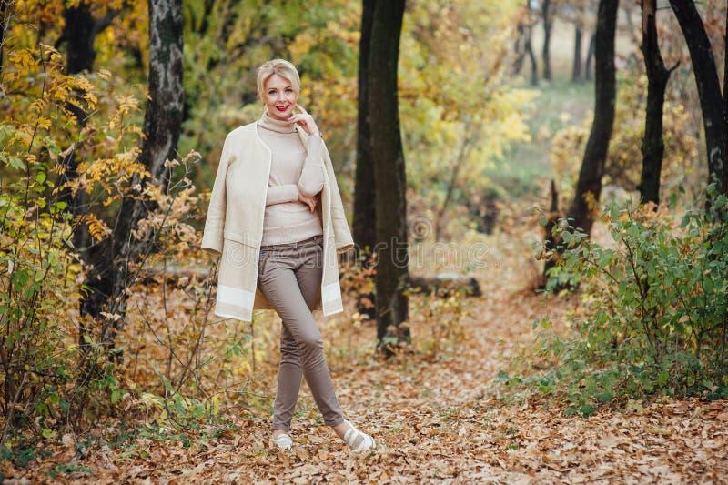 Красивая молодая белокурая женщина тратя время в парке осени стоковые фотографии rf