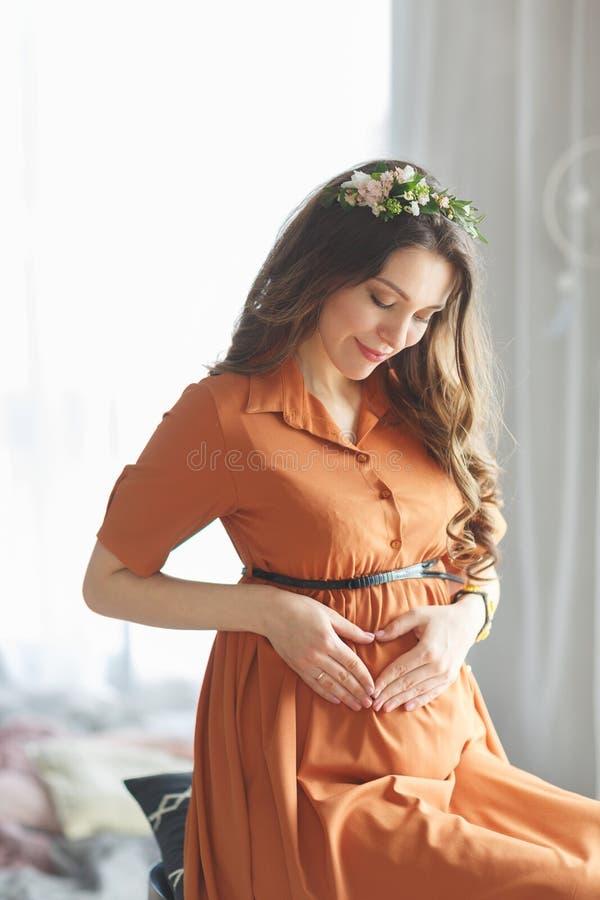 Красивая молодая беременная девушка с венком цветков на ее голове в коричневом платье со шнурком сидит около окна и стоковое изображение rf