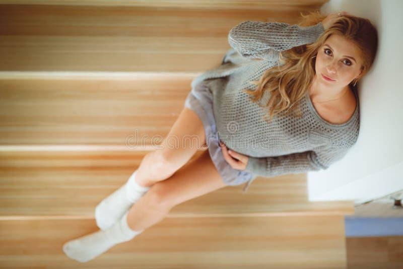 Красивая молодая беременная женщина сидит на шагах деревянной лестницы стоковые фото