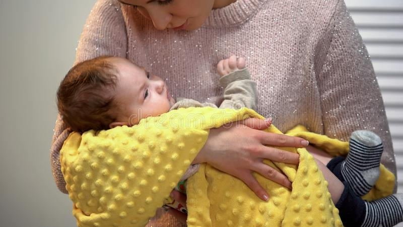 Красивая молодая дама поя меньшему младенцу для того чтобы спать, держащ осторожно в оружиях стоковая фотография rf