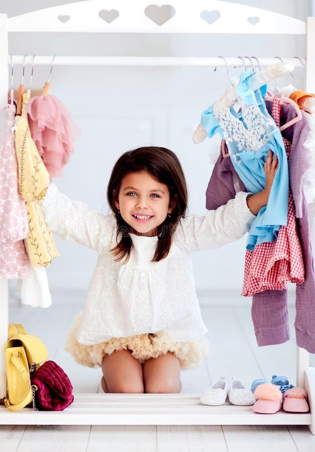 Красивая молодая девушка, веселящаяся среди одежды, выбирающая партийное платье в гардеробе стоковые изображения