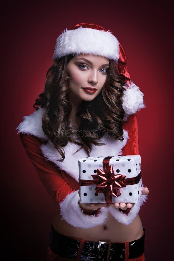 Красивая молодая девушка Санты с подарком на красной предпосылке стоковое изображение