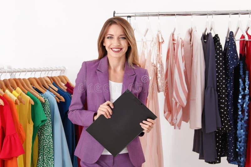 Красивая молодая доска сзажимом для бумаги удерживания стилизатора около шкафа с дизайнерской одеждой стоковая фотография rf