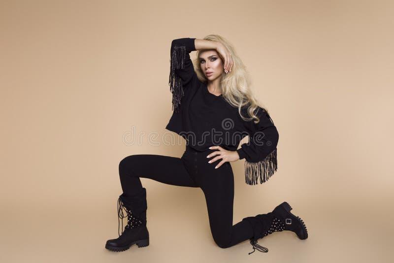 Красивая, молодая женская модель в одежде осен-зимы, военные hoodie и прозодежды и ботинки на бежевой предпосылке стоковая фотография rf