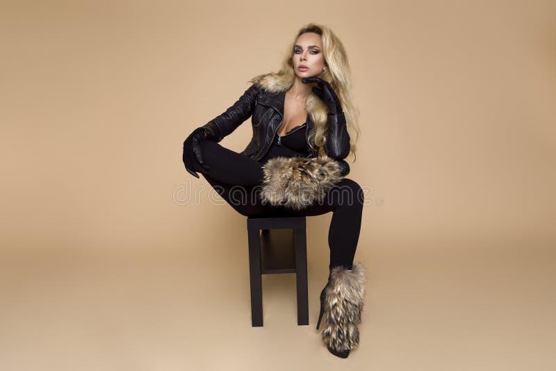 Красивая, молодая женская модель в одежде осен-зимы, военные hoodie и прозодежды и ботинки на бежевой предпосылке стоковые изображения