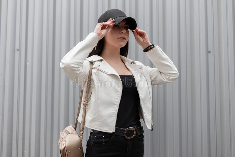 Красивая молодая женщина брюнета с ультрамодным рюкзаком золота в винтажной белой кожаной куртке в футболке в черных джинсах стоковая фотография rf