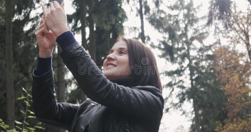 Красивая молодая женщина брюнет принимая Selfie используя Smartphone Закройте вверх счастливой девушки используя Smartphone Outdo стоковые фотографии rf