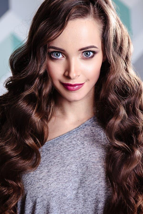 Красивая молодая женщина брюнет с длинным составом вьющиеся волосы и вечера, портретом красоты моды стоковое изображение