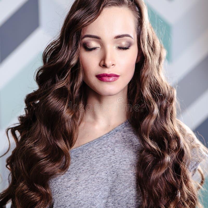 Красивая молодая женщина брюнет с длинным составом вьющиеся волосы и вечера, портретом красоты моды стоковые изображения