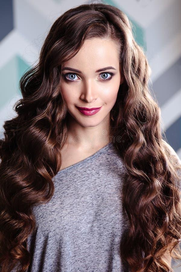 Красивая молодая женщина брюнет с длинным составом вьющиеся волосы и вечера, портретом красоты моды стоковые изображения rf