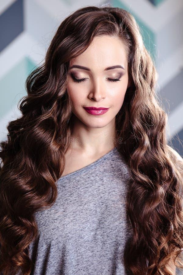 Красивая молодая женщина брюнет с длинным составом вьющиеся волосы и вечера, портретом красоты моды стоковое фото