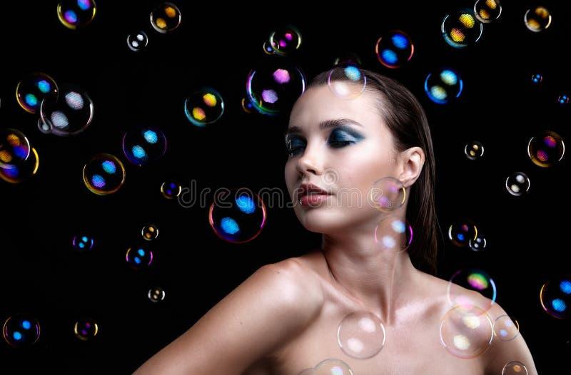 Красивая молодая женщина брюнет с пузырями мыла на черном backgr стоковые фото