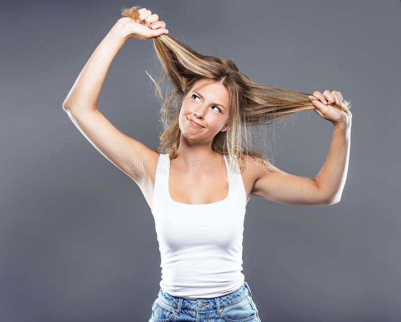 Красивая молодая женщина вытягивая ее волосы над серой предпосылкой стоковые изображения rf