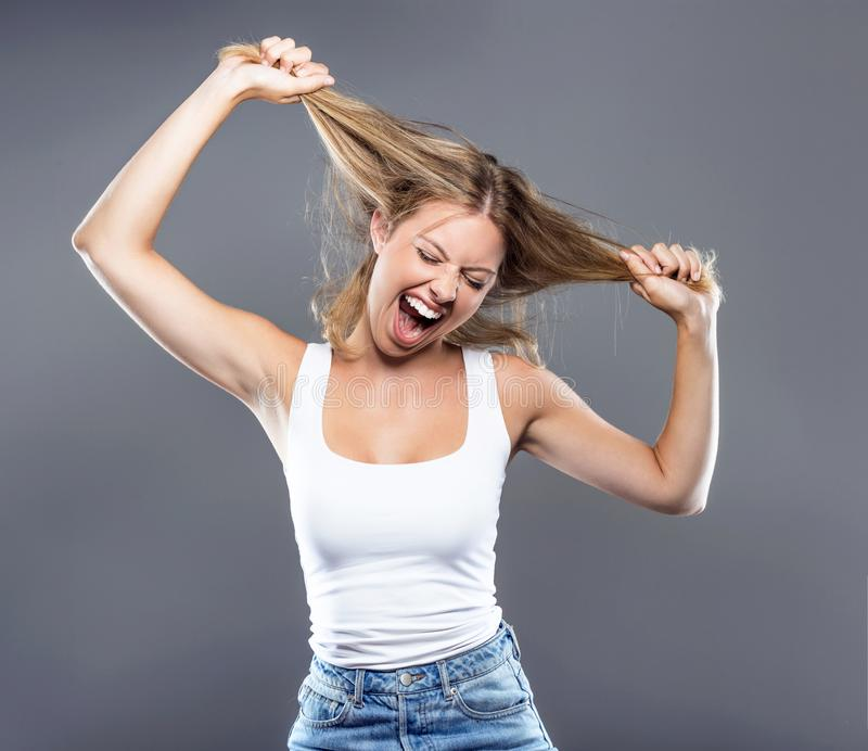 Красивая молодая женщина вытягивая ее волосы над серой предпосылкой стоковое фото rf
