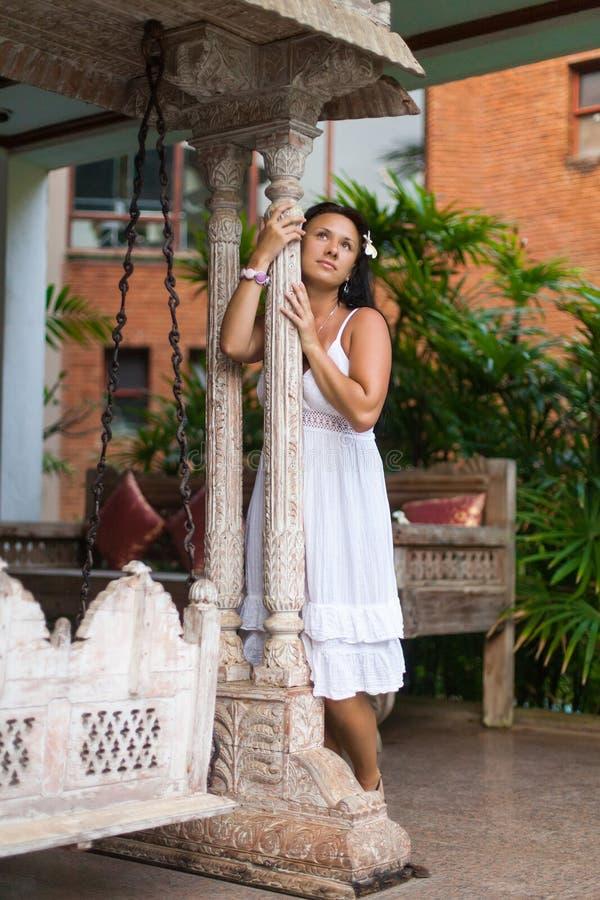Красивая молодая женщина в белом платье мечтая о винтажном качании в саде перемещение и концепция лета стоковое фото