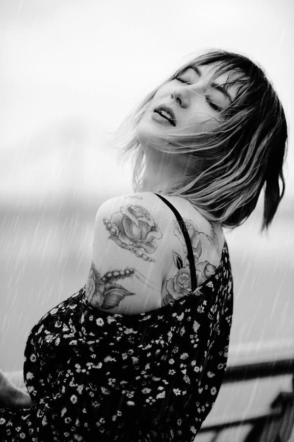 Красивая молодая женщина в дожде с татуировкой на ее волосах рук, чувственного и нежных, влажных черная белизна стоковое изображение rf