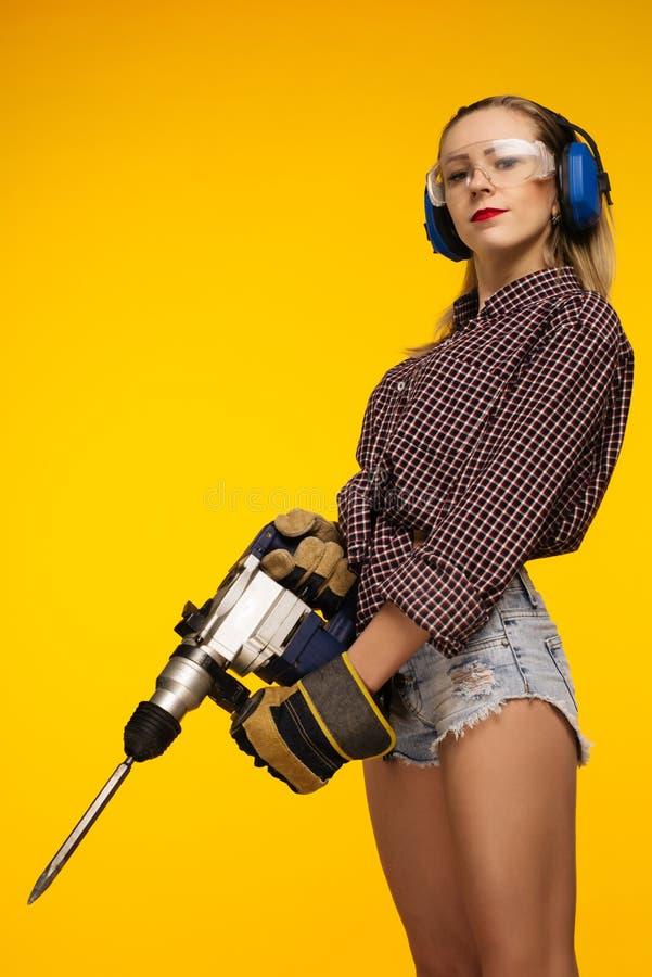 Красивая молодая женщина в изумленных взглядах и сверле перфоратора удерживания стоимости наушников изолированном на желтой предп стоковое фото rf
