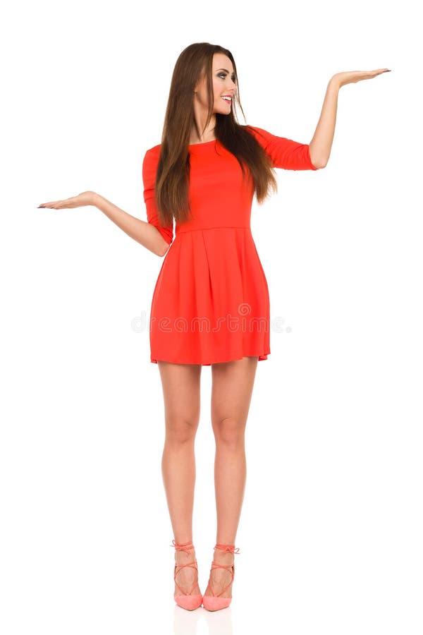 Красивая молодая женщина в красном мини платье стоит с повышением рук и смотрит прочь стоковые фотографии rf