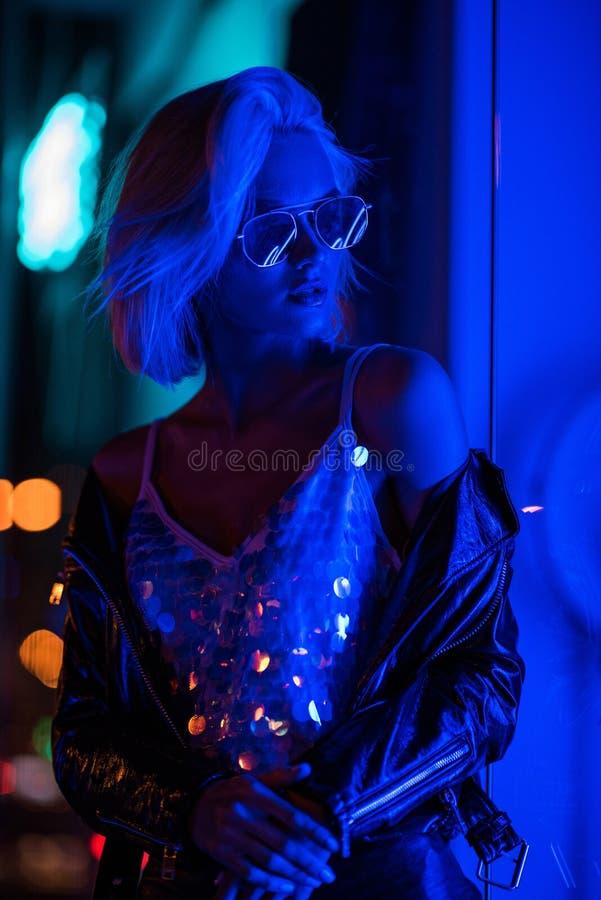 красивая молодая женщина в лоснистой верхней части танка и солнечные очки на улице вечером вниз стоковые изображения