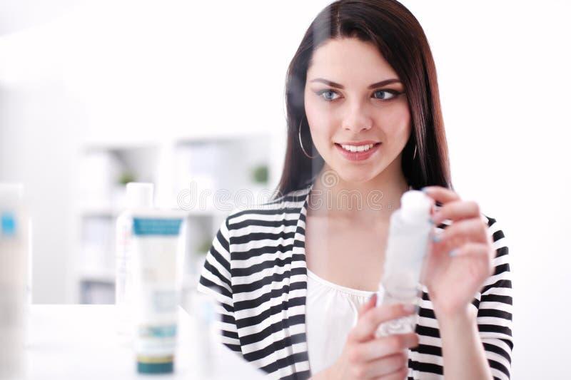 Красивая молодая женщина в магазине держа бутылку стоковое фото