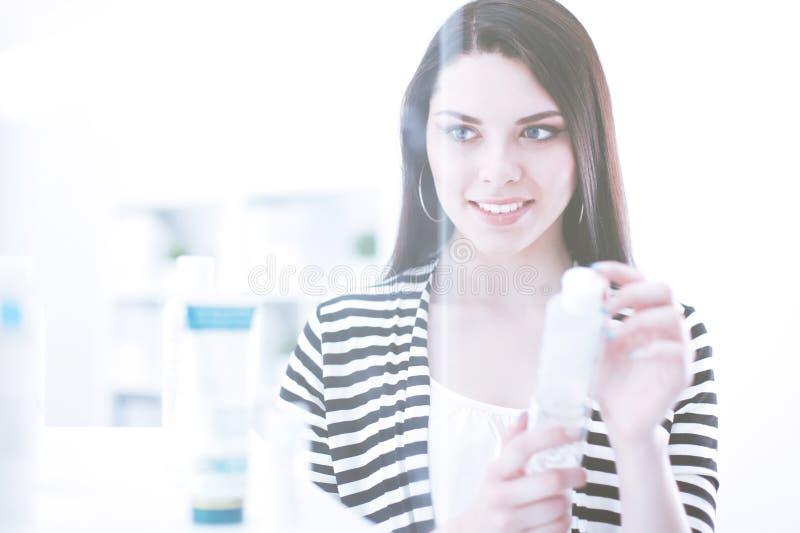 Красивая молодая женщина в магазине держа бутылку стоковая фотография rf