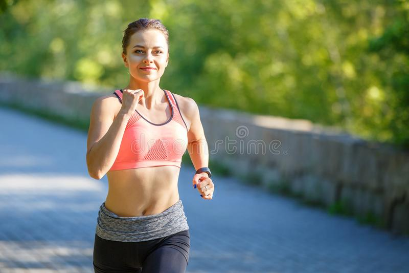 Красивая молодая женщина в розовой верхней части jogging в парке стоковая фотография