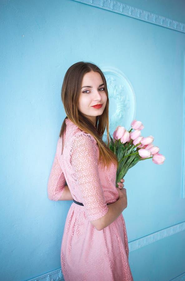 Красивая молодая женщина в розовом удерживании платья в руках скачет букет цветков тюльпанов на голубой предпосылке стены стоковое изображение rf