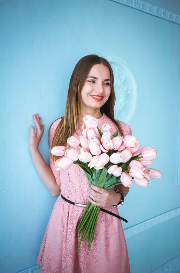 Красивая молодая женщина в розовом удерживании платья в руках скачет букет цветков тюльпанов на голубой предпосылке стены стоковые фотографии rf